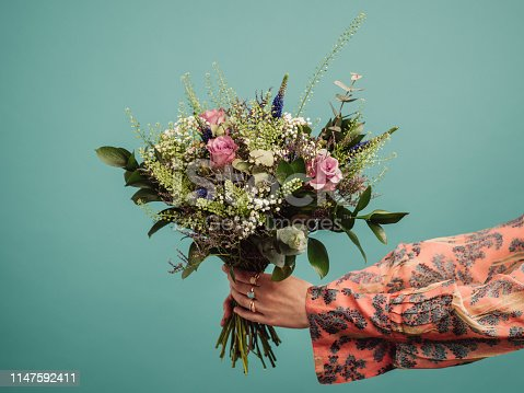 Woman holding a big bouquet of flowers, arms only Photo of hands and flowers in studio against turquoise