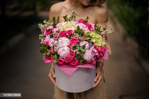 Woman holding a big box filled with a lot of beautiful pink roses and peonies