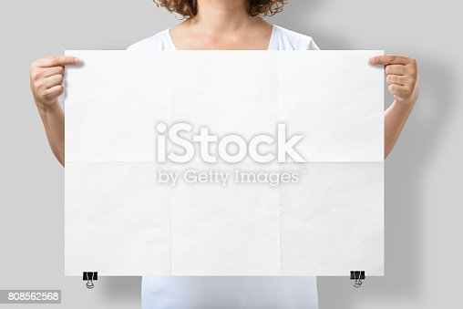 istock Woman holding a blank A2 poster mockup isolated on a gray background. 808562568