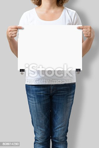 istock Woman holding a blank A3 poster mockup isolated on a gray background. 808614290