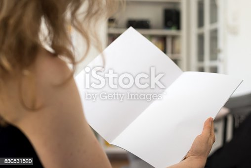 istock Woman holding a blank brochure with copy space in her hands 830531520