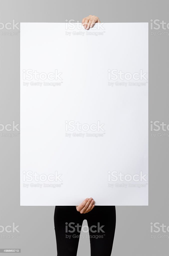 Woman holding a blank poster, square 70x100, mock up. stock photo