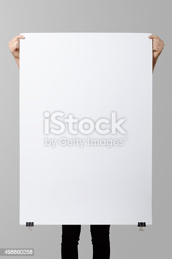 istock Woman holding a blank poster, square 70x100, mock up. 498860258