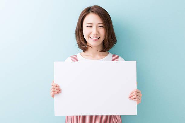 空の看板を持つ女性 - 東洋民族 ストックフォトと画像