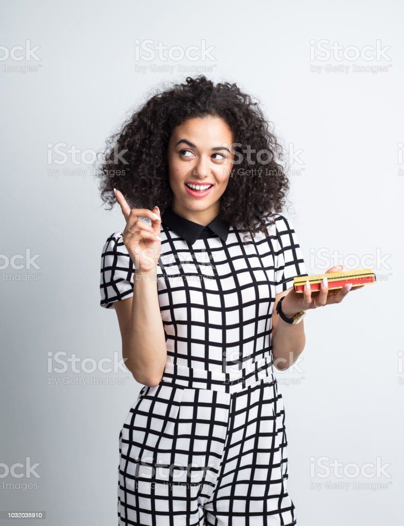 Woman holding a book and pointing away Portrait of attractive young woman holding a book and pointing away on grey wood background 20-24 Years Stock Photo