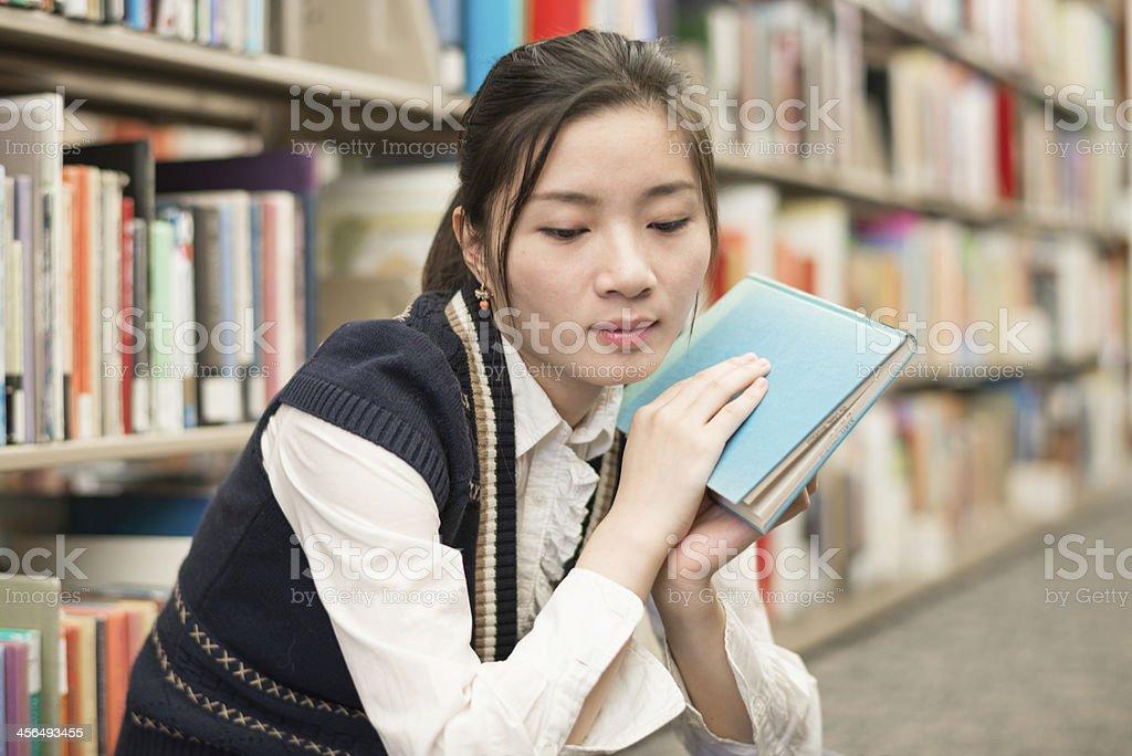 Woman holding a book near bookshelf royalty-free stock photo