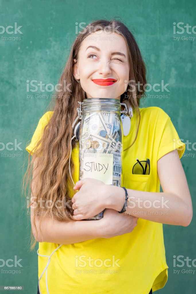 Woman holding a bottle full of money savings for study stock photo