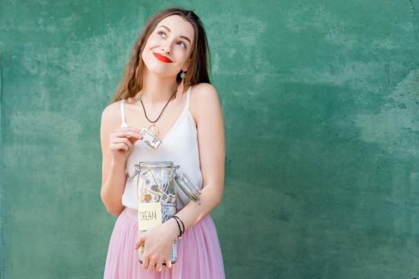 お金の節約のフルボトルを保持している女性 ストックフォト