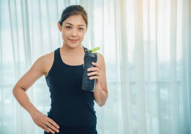 Eine Frau hält eine Flasche Protein ergänzt auf Muskel-Getränk, Gesundheitswesen, kräftig und schön zu stärken. – Foto