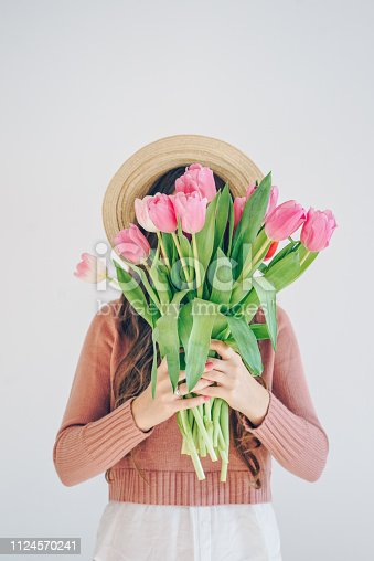 Unrecognizable woman holding a bunch of pink tulips