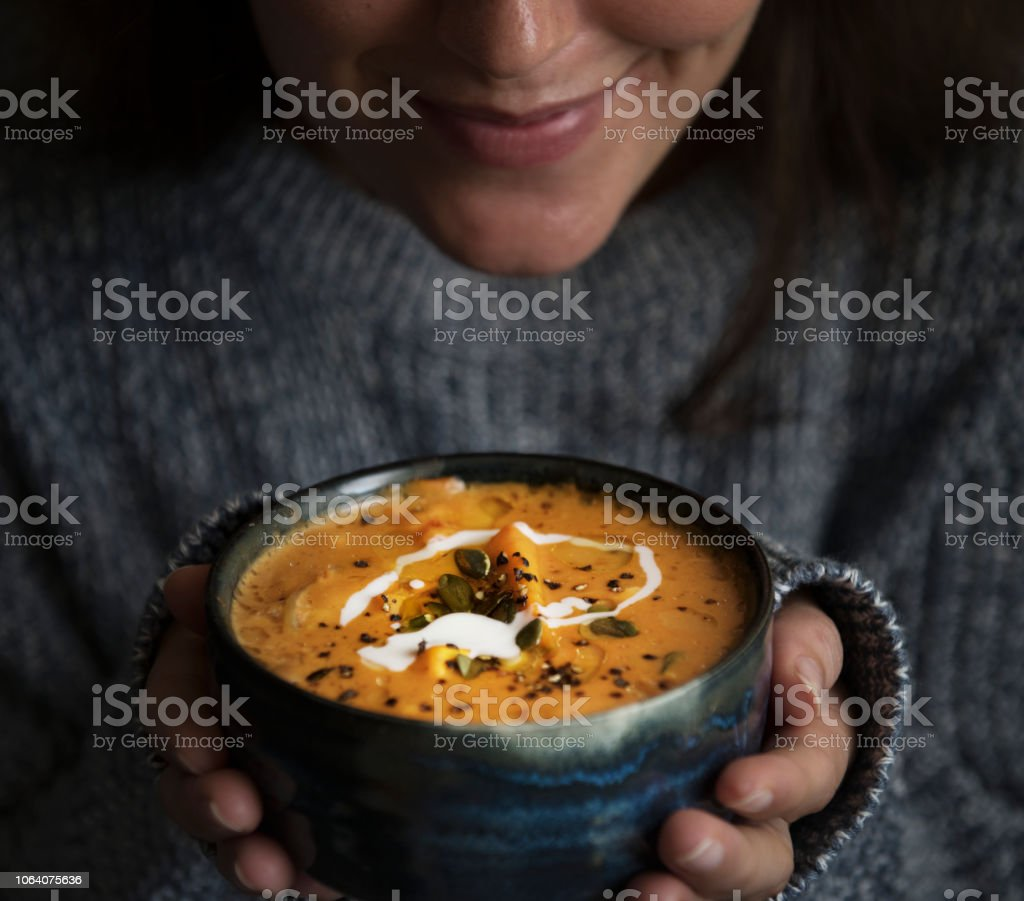 Woman holding a bowl of soup food photography recipe idea stock photo
