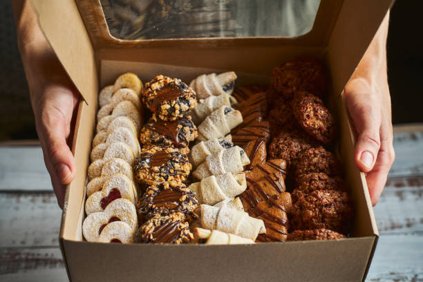 Woman holding a box filled with mini Christmas pastry cakes Woman holding cardboard take away box filled with Christmas pastry, close up cookie stock pictures, royalty-free photos & images