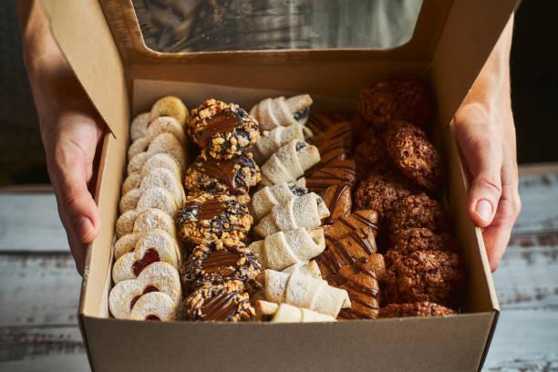 vrouw het houden van een doos gevuld met mini kerst gebak taarten - deeggerechten stockfoto's en -beelden