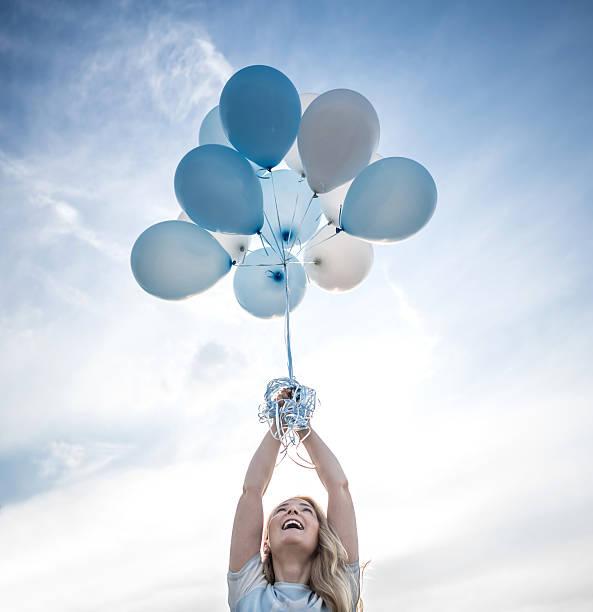 mulher a segurar um bando de balões de hélio ao ar livre - mulher balões imagens e fotografias de stock