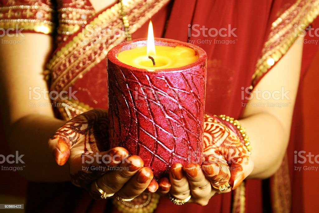 A woman holding a candle while praying  royalty-free stock photo