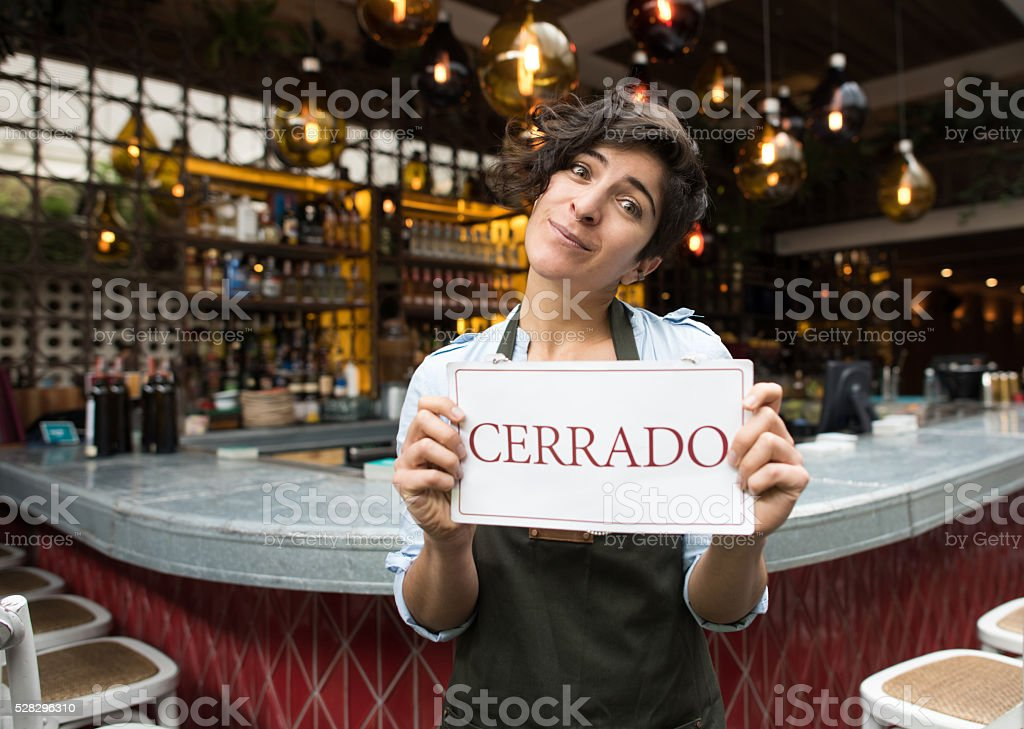 Woman holding a closed sign in Spanish at a restaurant stock photo