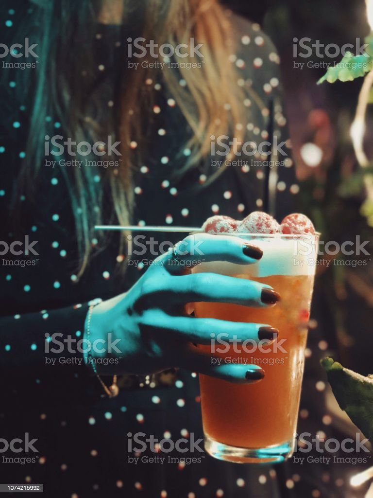 Woman holding a cocktail in hand stock photo