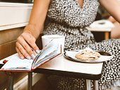 Young woman sitting at a cafe with her agenda