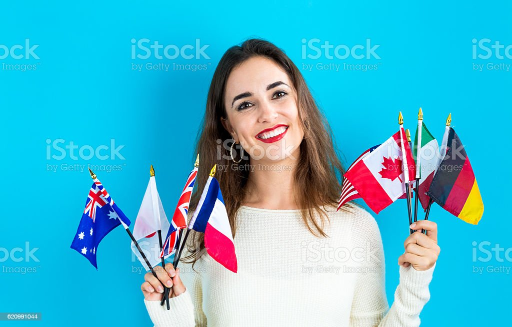 Woman holding a collection of international flags foto royalty-free