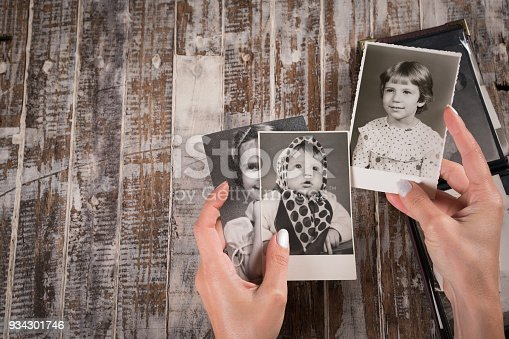 istock Woman holding a collection of old photographs 934301746