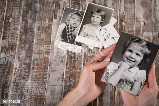 istock Woman holding a collection of old photographs 934304028