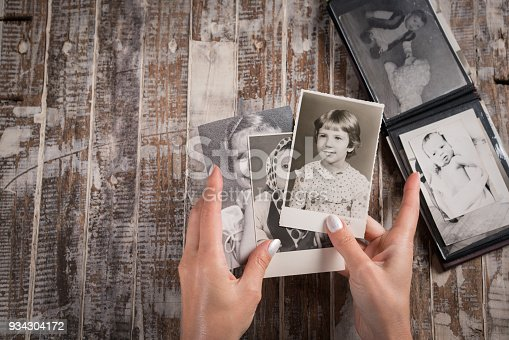istock Woman holding a collection of old photographs 934304172