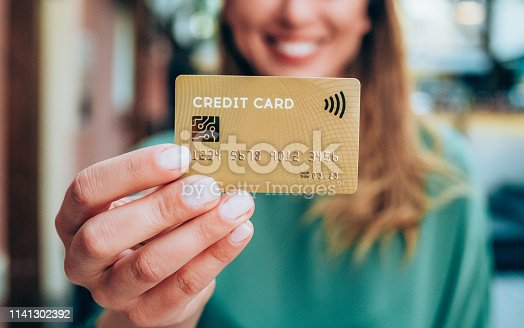 Beautiful young female shopper holding a credit card - focus on foreground.