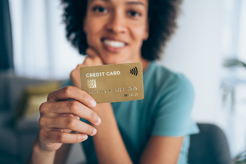 Beautiful young african-american woman holding a credit card - focus on foreground.