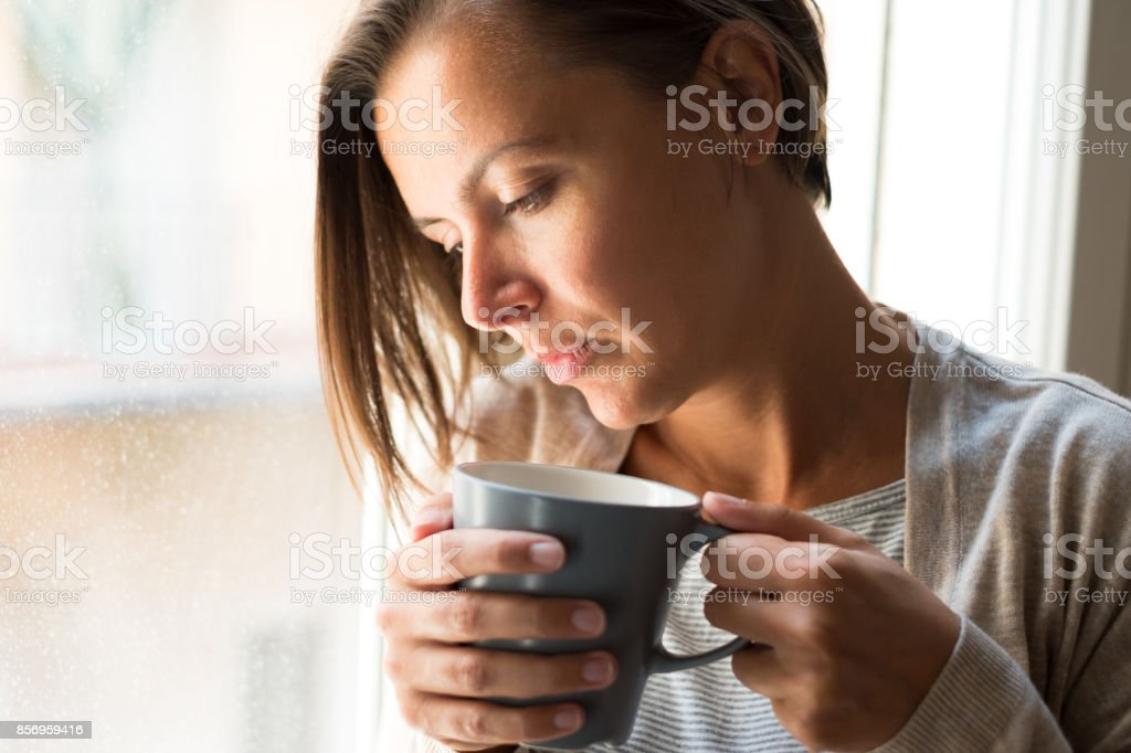 Woman holding a cup of coffee portrait next to a window stock photo