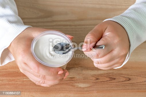 Woman holding a cup of yogurt and spoon in hand on the table. Yogurt made from milk fermented by added bacteria, often sweetened and flavored. Selective focus.