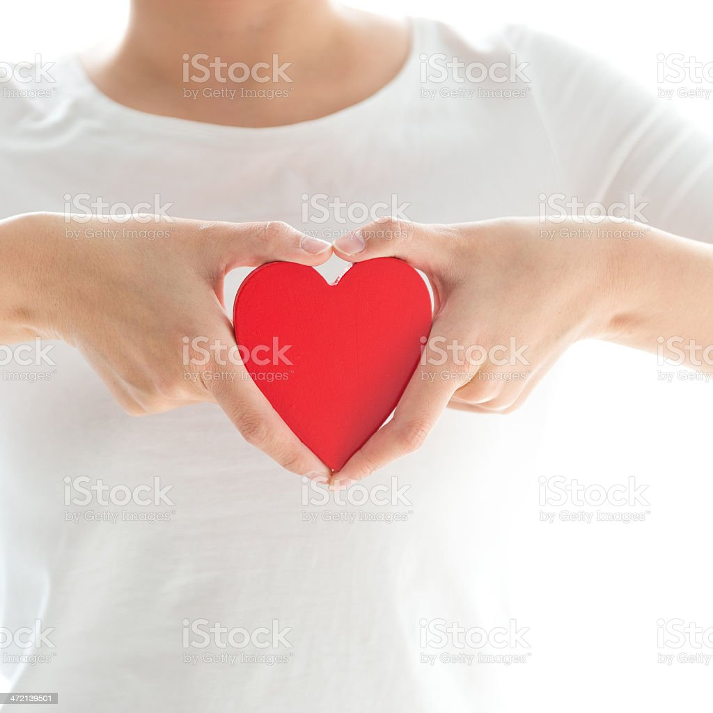A woman holding a cut out of a heart next to her chest stock photo