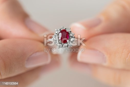 Hands holding diamond ring. Ruby.