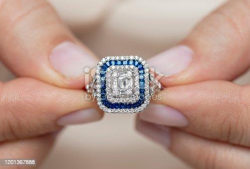 Hands showing diamond. Sapphire blue.
