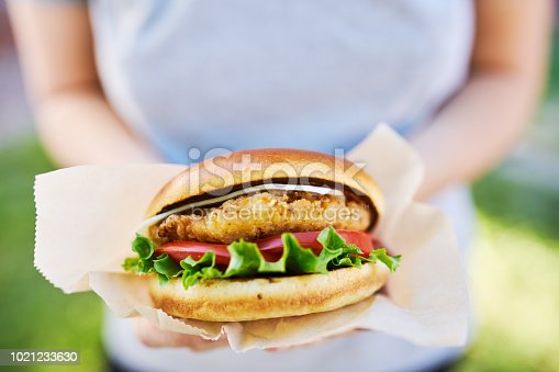 woman holding a fast food style crispy chicken sandwich shot with selective focus