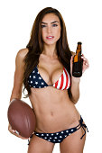 Sexy woman wearing an American flag style bikini and holding a beer and football while being isolated on white background