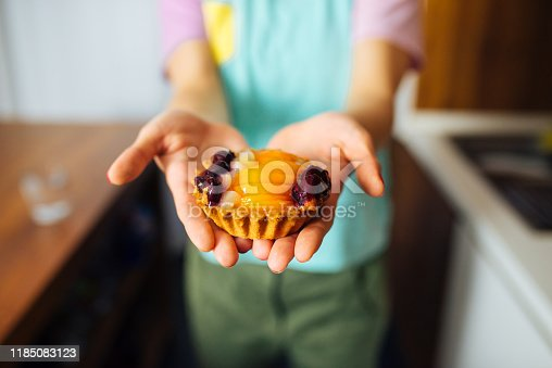 Close up View of Woman Holding a Delicious Cake with Berries, Blurred Background.