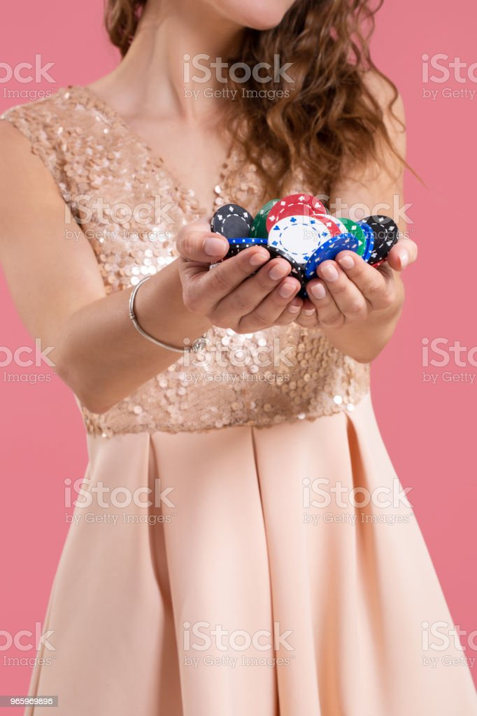 Woman holding a gambling chips in her nands on pink background. Close-up - Royalty-free Addiction Stock Photo