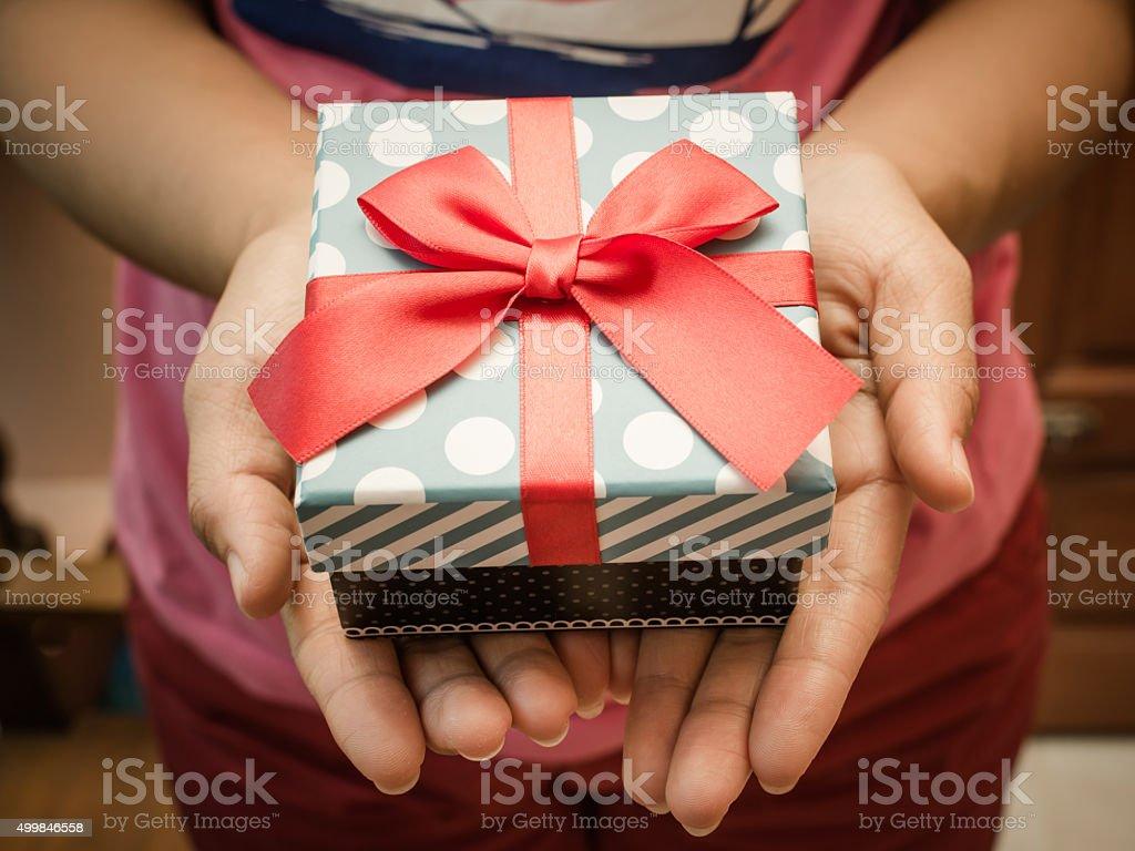 Frau mit einem Geschenk-box in einer Geste des Teilens – Foto