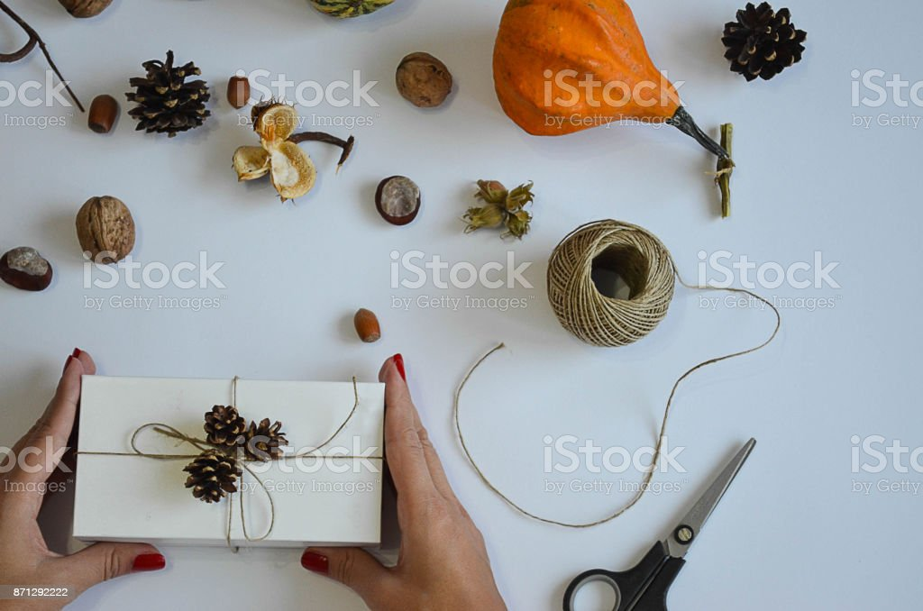 Woman holding a gift box in a gesture of giving stock photo