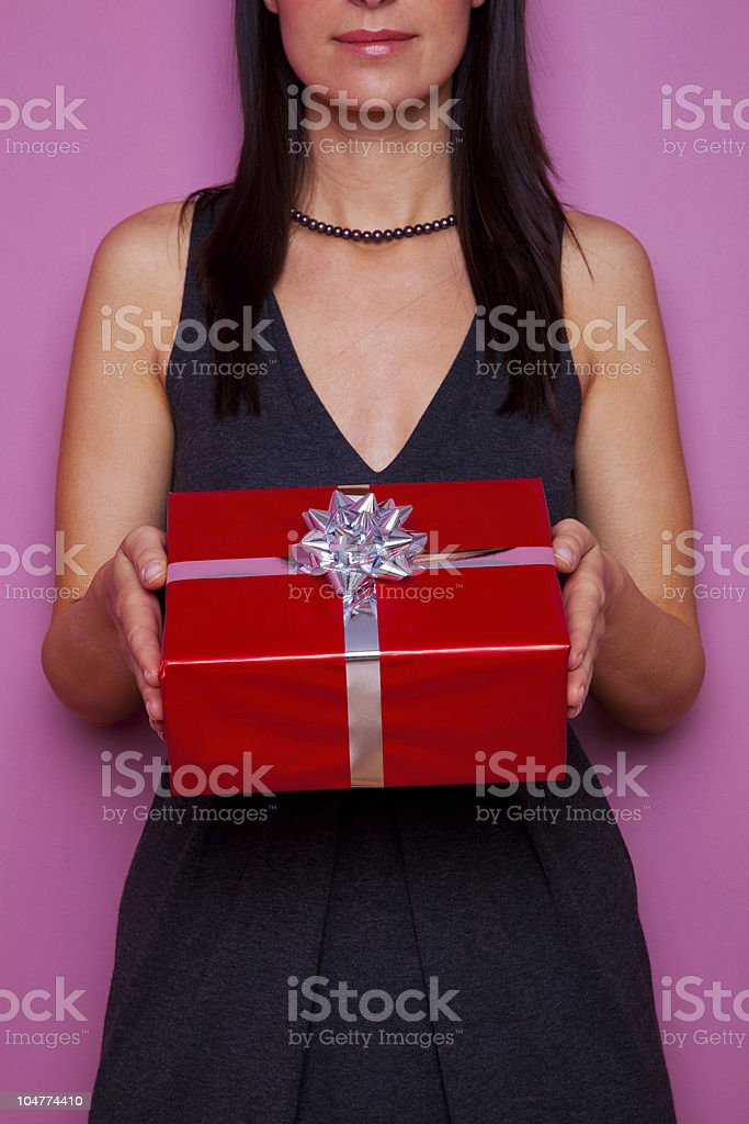 Woman holding a gift wrapped in red paper royalty-free stock photo