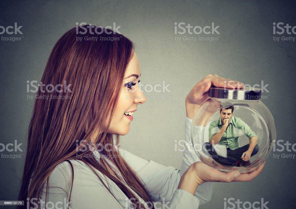 Mulher segurando um frasco de vidro com homem aprisionado dentro - foto de acervo