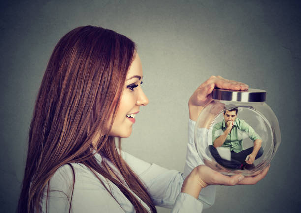 Woman holding a glass jar with imprisoned man in it Woman holding a glass jar with imprisoned man in it battle of the sexes concept stock pictures, royalty-free photos & images