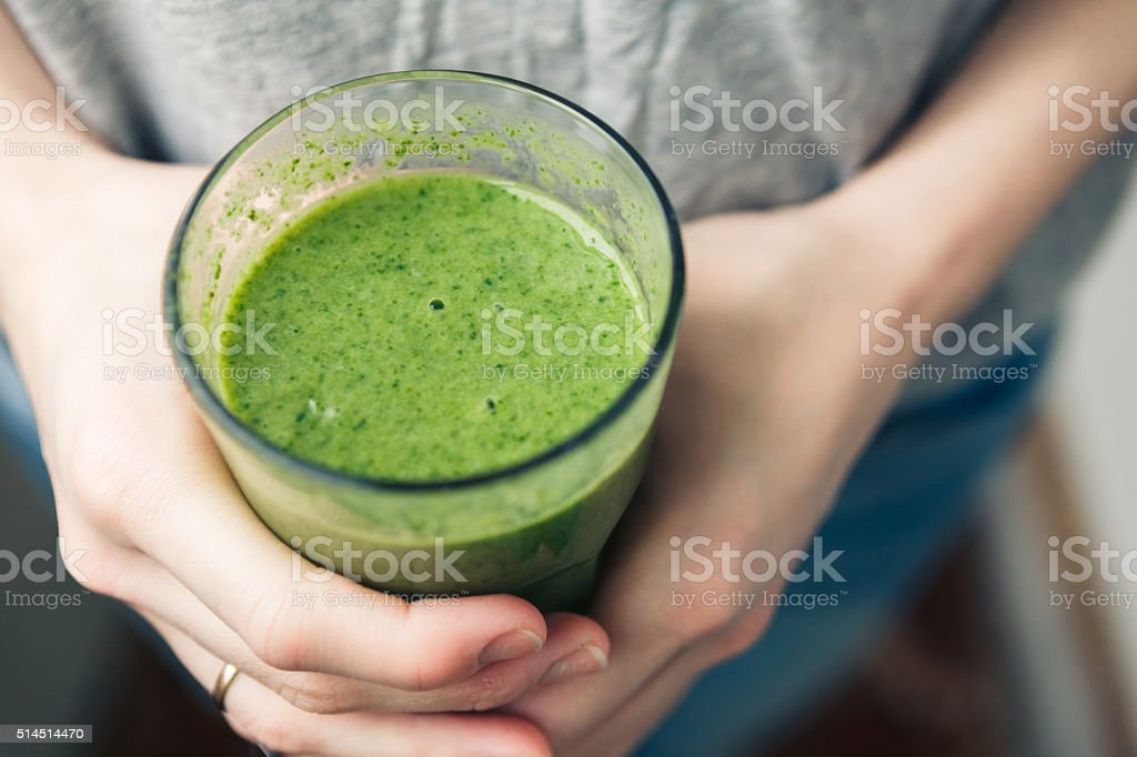 woman holding a glass of green smoothie stock photo