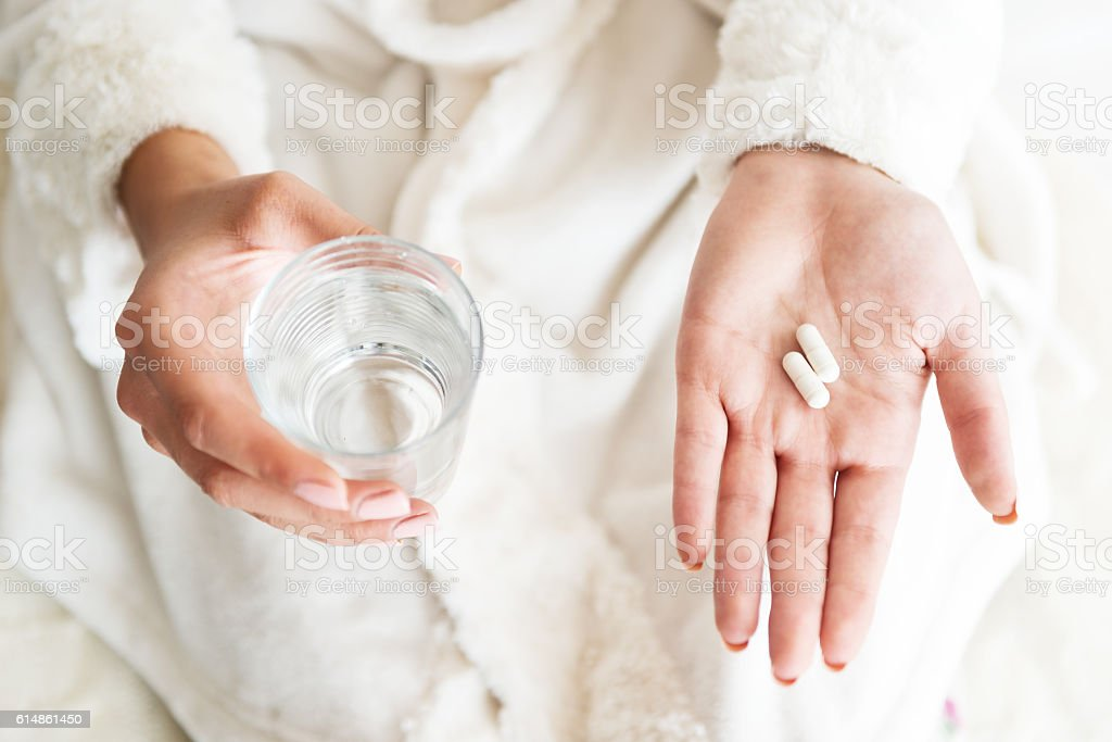 Woman holding a glass of water and pills, detail stock photo