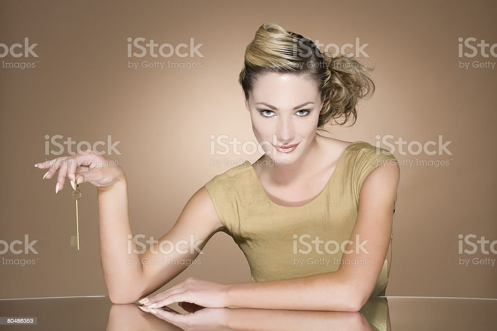 Woman holding a gold key stock photo