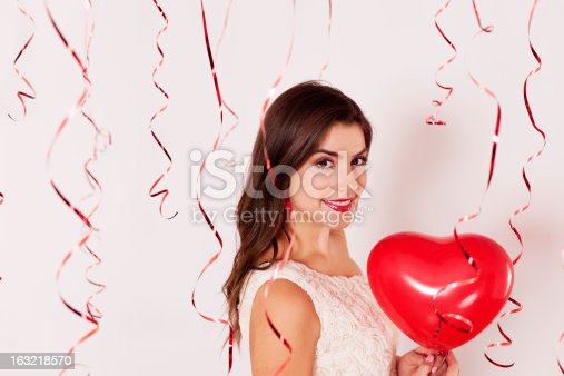 579443552istockphoto A woman holding a heart balloon on a Valentines day party 163218570