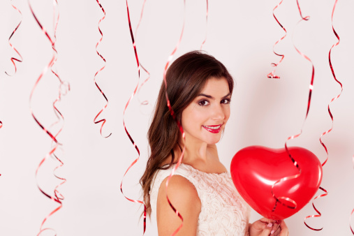 579443552 istock photo A woman holding a heart balloon on a Valentines day party 163218570
