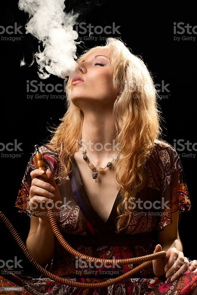 A woman holding a hookah and blowing smoke from her mouth stock photo