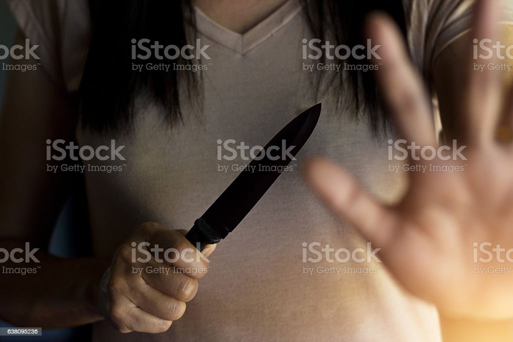 Woman holding a knife in hand while defending herself - foto de acervo
