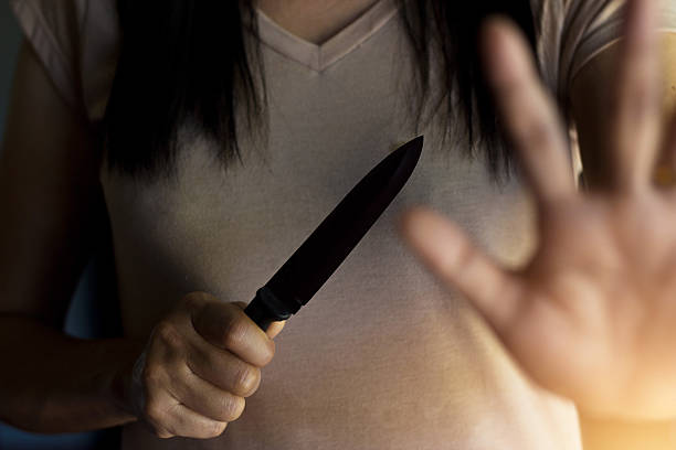 woman holding a knife in hand while defending herself - killer stock pictures, royalty-free photos & images